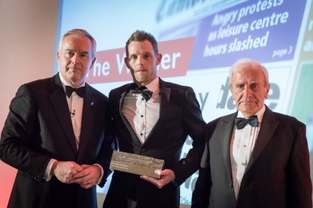 Chris Betteley holds his award flanked by Huw Edwards, left, and Vincent Kane OBE