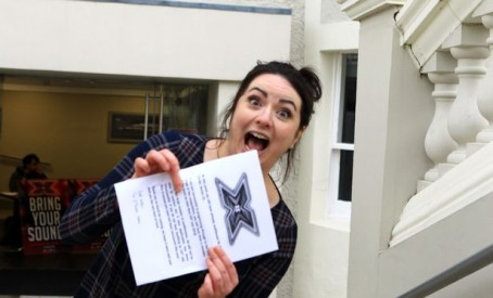 Zara with a printout confirming her participation in the audition