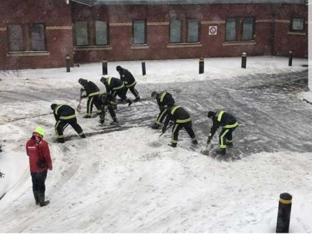 Firefighters clear away snow from a hospital car park in Tiverton - one of the stories which saw Devon Live reach its page view record