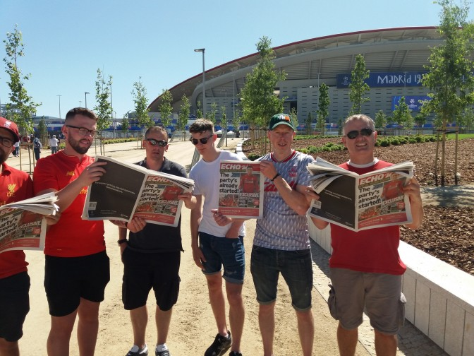Supporters reading today's Madrid edition of the Liverpool Echo at the Wanda Metropolitano Stadium