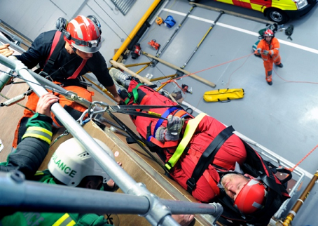 Neil Hudson is lowered to the ground on a stretcher as part of the training exercise.