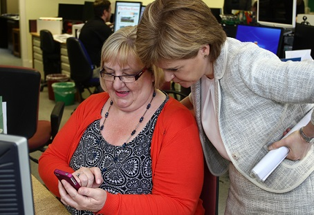 Oban Times chief sub Lesley McKerracher, who has been with the company for 26 years, shows off a picture of her granddaughter to Nicola Sturgeon.