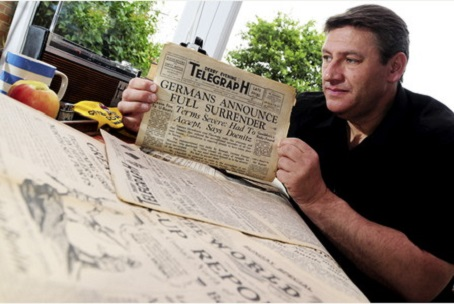 Steve Griffiths is pictured with an edition of the Derby Telegraph announcing the end of the war.